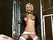 Luscious blonde gets caged and lets a horny dude touch her tits before she gets her mouth gagged with a red ball, her nipples pulled and her pussy whipped wearing her black blouse and blue and white skirt then gets naked and tied on an X bar and gets her