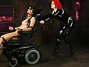 Naked hottie gets pinned down by metal pipes on a wooden floor then gets her pussy whipped by a redhead chick in black latex outfit before she gets tied on a black wheel chair and gets gagged by a red ball then gets stepped on her mouth.