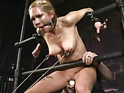 Lusty blonde gets cuffed on metal pipes then gets her mouth gagged with a red ball before she gets her hot tits and pussy clipped and pulled before she lays prone and tied on a black bed then gets her sweet pussy vibrated.