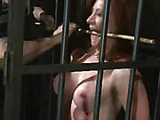 Foxy redhead lays down naked and gets strapped on a wooden bed then gets her smoking hot body whipped and her lusty pussy vibrated before she gets locked in a cage and gets sqeezed with a bunch of sticks.