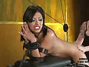Gorgeous hottie sits and tied on an iron chair then gets gagged by a red ball before she lets a sexy redhead in violet shirt and black pants stab her wet twat with a steel dildo before she gets leaned over and bounded on a black bench then gets her pussy