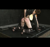 Alluring redhead gets her head and hands locked by a wooden cuff while gagged and blindfolded before she gets bent over and strapped on different pipes then gets her hot ass whipped and her juicy tits clipped with laundry pins.