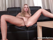 Blonde innocent girl on the black couch rubs her clit which makes her pussy wet
