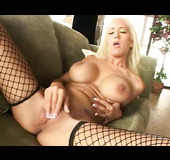 Big boobed blonde in fishnet hose spreading on the green couch while rubbing and fingering shaved vagina