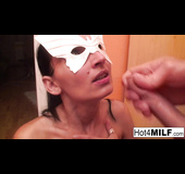 Mask-wearing tanned brunette sucking a massive cock