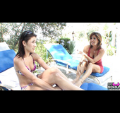 Busty redhead in red dress seducing and massaging young brunette outdoors on the lounge chair
